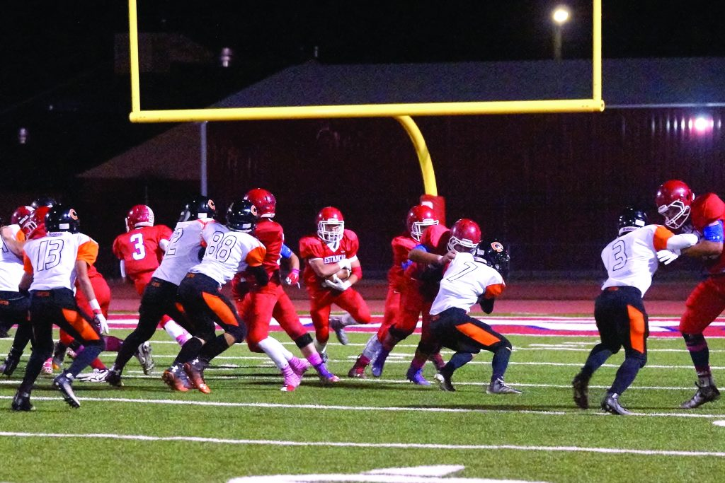 Estancia's offensive line opening up a hole for running back Zeke Tapia during last Friday's home game against Clayton. Photo by Julie Carter.