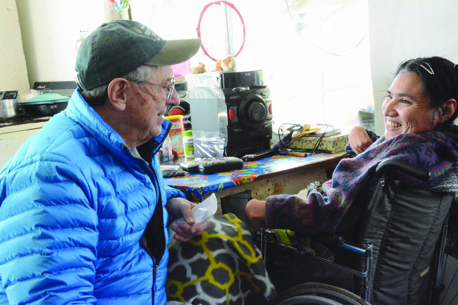 Jim Gallagher making a handicapped woman smile in her home in Juárez. Photo by Morgan Smith.