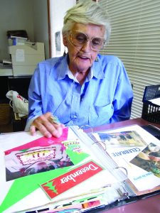 The late Doris Lark showing off the scrapbooks that she made at The Independent in March 2014. Photo by Leota Harriman.