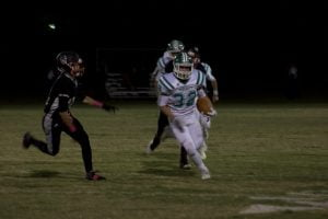 Moriarty's Elijah Tapia carrying the ball against NMMI. Photo by Angelina Rose Lane.