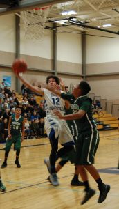 East Mountain's Isiah Padilla flying past a Thoreau Hawk for a layup during last Thursday's game. Photo by G. Demarest.